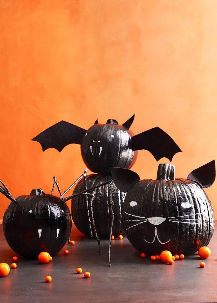 eine orange wand und vier schwarze diy fledermäuse mit weißen augen und mit schwarzen flügeln aus papier und mit weißen scharfen zähnen, fledermaus basteln aus einem kürbis, lustige kürbisgesichter malen