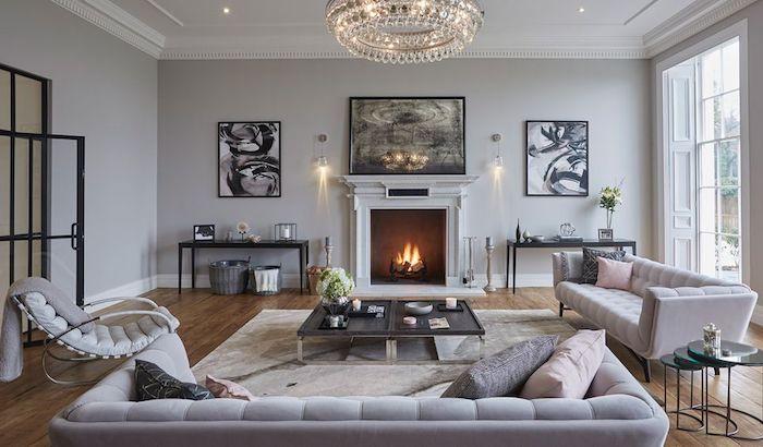 wanddeko wohnzimmer, kamin im retro stil, runder kronleuchter, zwei bilder in schwarz und grau