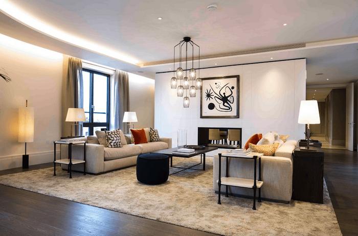 wanddeko wohnzimmer, pandelleuchte über dem kaffeetisch, großer teppich, stehlampen