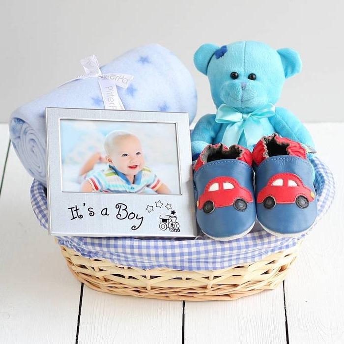 Idee für Taufgeschenk, Korb voller Geschenke, Baby Decke, blauer Kuschelbär, Babyschuhe und Bilderrahmen