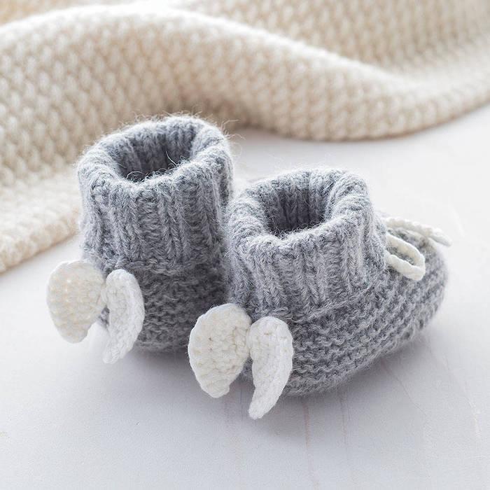 Selbstgestrickte graue Babyschuhe mit weißen Flügeln, Idee für süßes Baby Geschenk