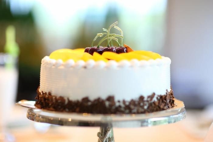 Geburtstagstorte Rezept, eine weiße Torte mit gelben Früchten und Kirschen gedeckt