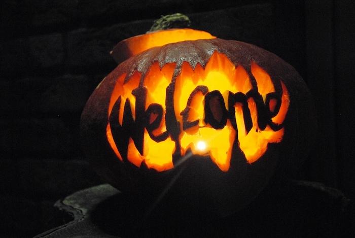 eine halloween dekoration mit einem großen orangen kürbis halloween mit einem welcome überschrift, einen kürbis schnitzen