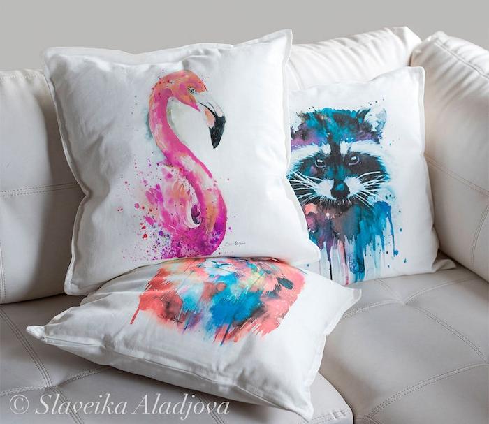 ein weißes sofa mit weißen kissen mit einem blauen waschbär und mit einer pinken flamingo