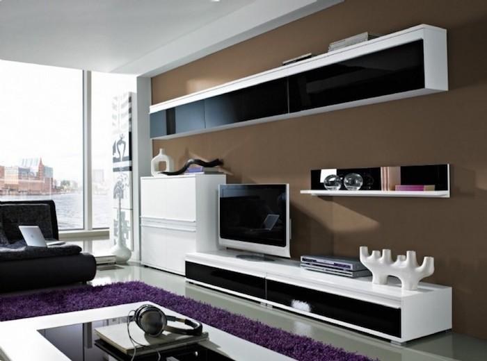 wohnzimmer einrichten, möbel in schwarz und weiß, lila teppich, braune wand