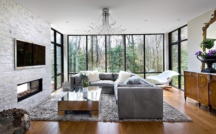 wohnzimmer ideen, steinwand mit ziegel motiv, fernsehwand, flauschiger teppich, boden aus holz
