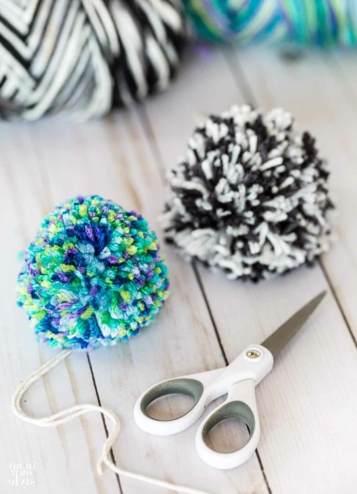 eine kleine Schere, bunte Pompons, Pompons Deko in zwei Farben, auf einem Tisch