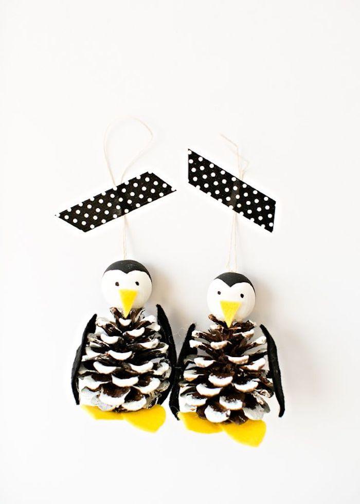 deko mit tannenzapfen basteln, zwei kleine schwarze pinguinen mit schwarzen augen und gelben beinen, pinguine aus tannenzapfen basteln