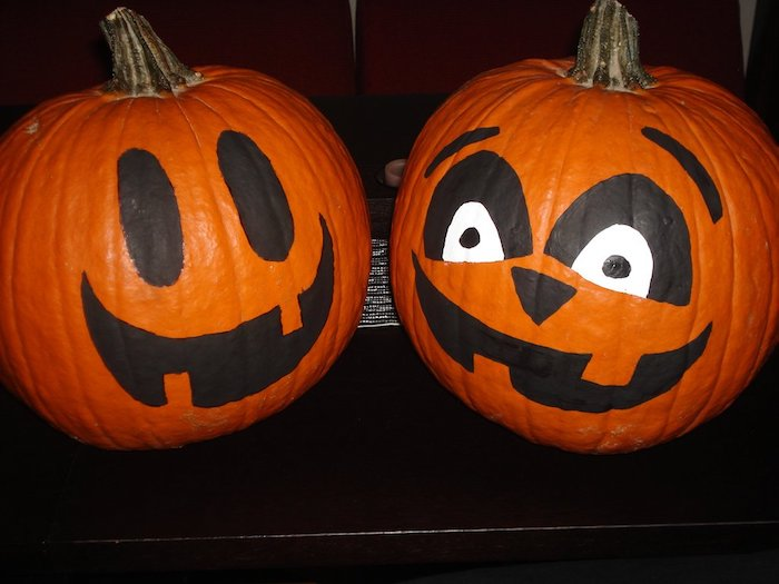 zwei orange kleine halloween kürbisse mit schwarzen großen augen und mit orangen zähnen, ein lustiges kürbis gesicht malen
