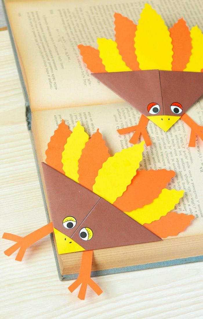 Lesezeichen falten, zwei Puten in oranger und gelber Farbe auf einem Buch