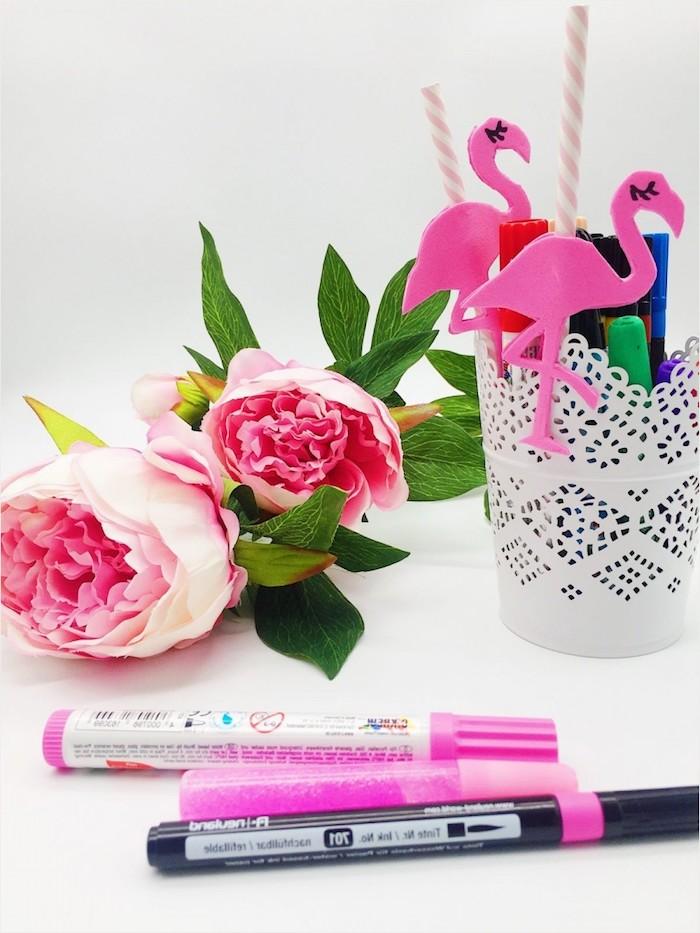 zwei rote rosen mit grünen blättern und ein glas mit zwei pinken strohhalmen mit zwei pinken flamingos und ein weißer tisch, flamingo deko basteln