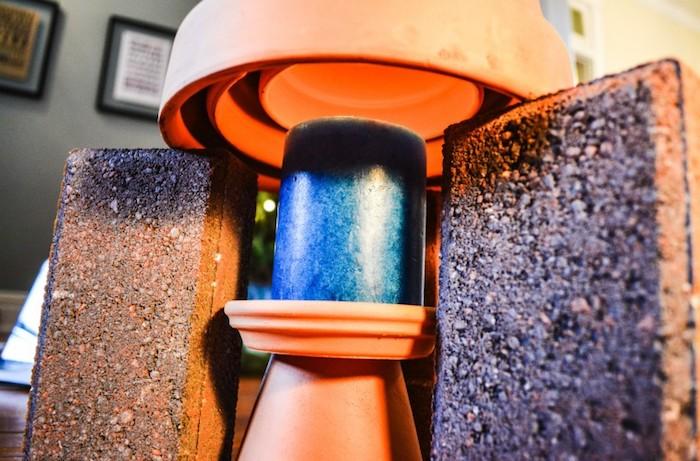 eine teelichtheizung schaffen mit einer blauen kerze, zwei braunen ziegeln und einem großen braunen blumentopf aus keramik, einen teelichtofen selber bauen. eine wand mit bilder mit schwarzen bilderrahmen