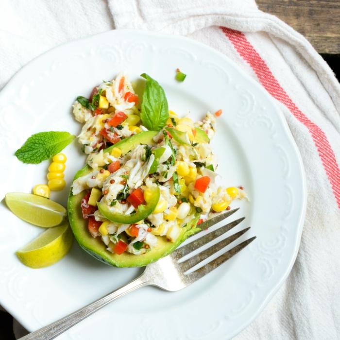 gesunde ernährung, gourmet speise zum genießen, salat in avocado, mais, fleisch, zitrone, basilikum