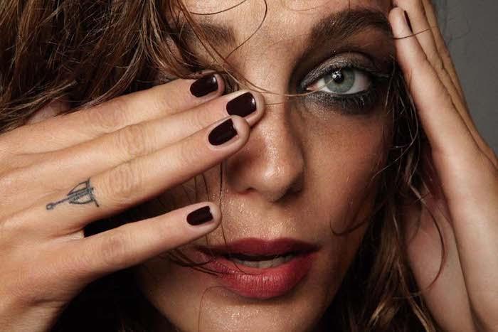 Kleines Tattoo am Ringfinger, schwarzer Nagellack, grüne Augen, dunkler Lidschatten und roter Lippenstift