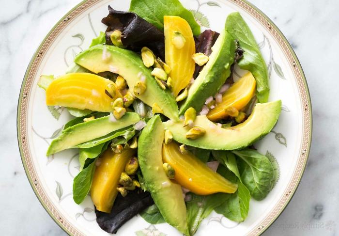 Avocado Mango Salat, Nüsse, Gartensalat in einem weißen Teller, rote Blätter