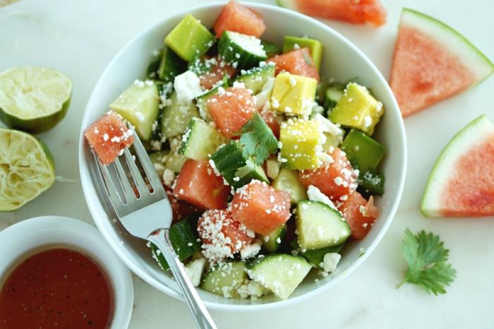Wassermelone, Avocado im Salat, mit Käse bestreut, Gurken und Petersilien auf dem Salat