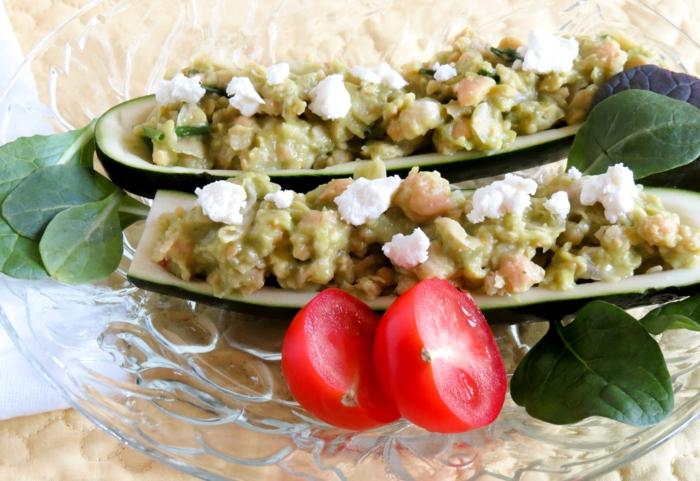zwei Avocado Stück, Kichererbse, Käse darauf, Avocado Tomaten Salat mit Kirschtomaten als Dekoration