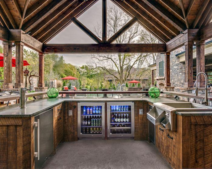 ein kleines braunes haus aus holz und in einem garten mit vielen grünen bäumen, eine außenküche selber bauen, eine outdooor küche mit einem waschbecken und einem kühlschrank