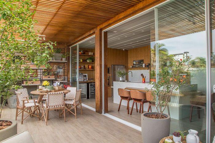 ein boden aus holz und brauer tisch und stühle aus holz, ein garten mit grünen pflanzen und eine kleine outdoor küche, außenküche holz ideen