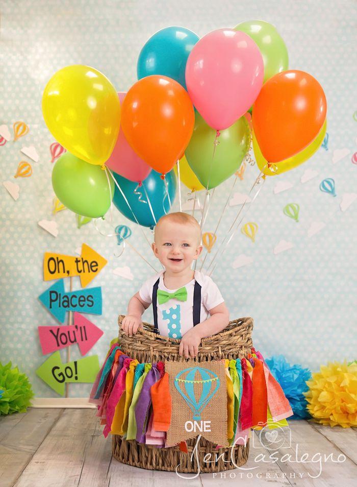 baby geschenk basteln, kleiner junge, viele bunte luftballons, großer korb, stücke bunter stoff