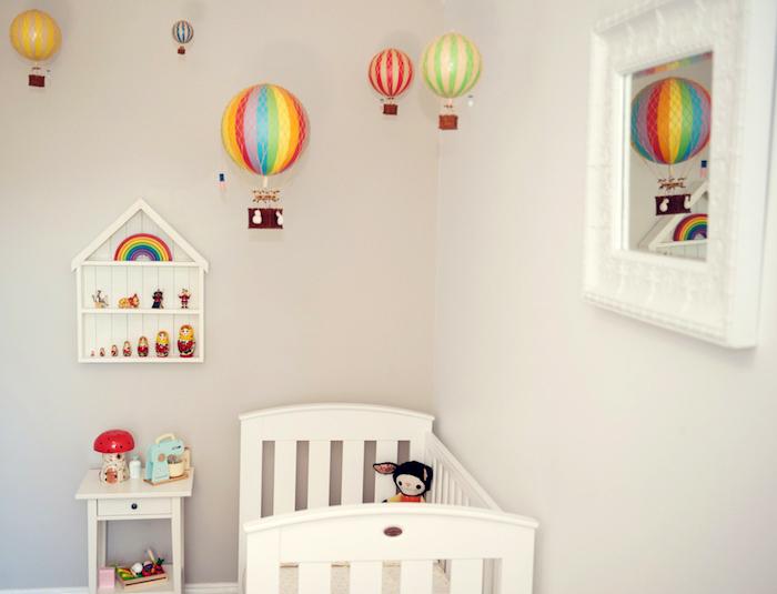 babyzimmer einrichten, baby geschenk basteln, viele bunte luftballons, spiegel mit großen rahmen, weißes babaybett