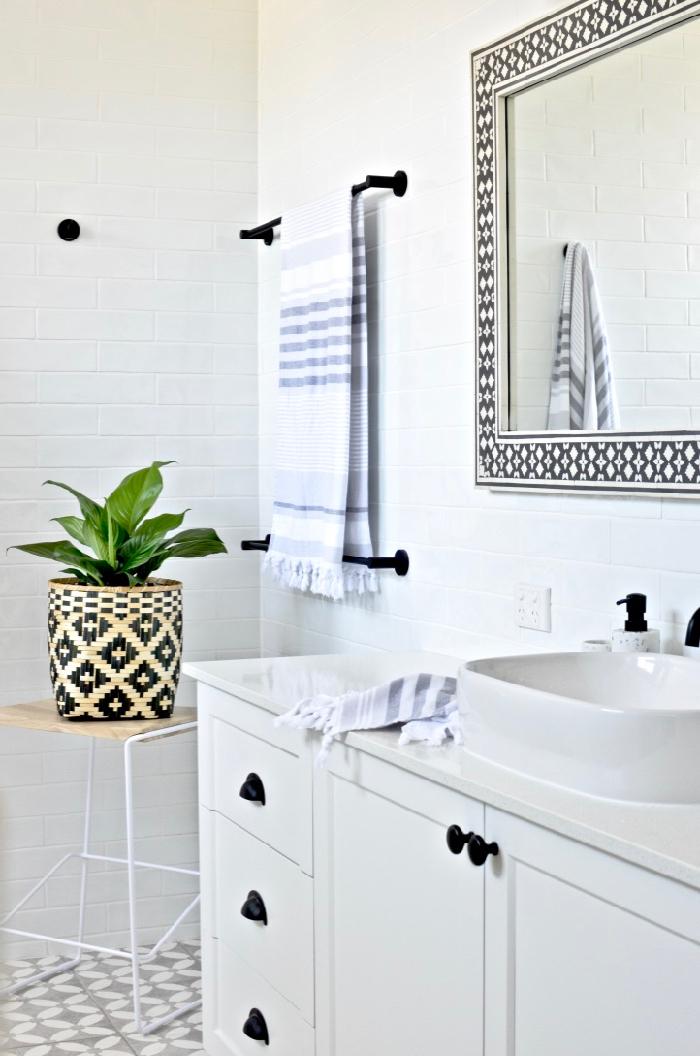 Badezimmereinrichtung Ideen, weiße Fliesen und Schränke, großer Spiegel und grüne Pflanze