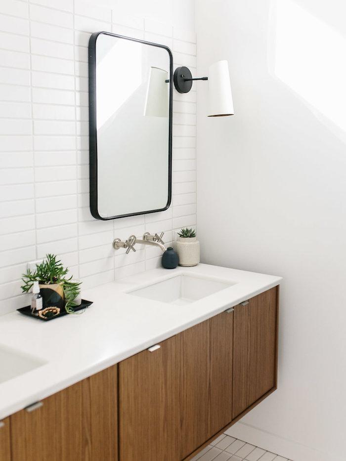 Badezimmereinrichtung in Weiß, weiße Fliesen und Holzoptik, großer Spiegel