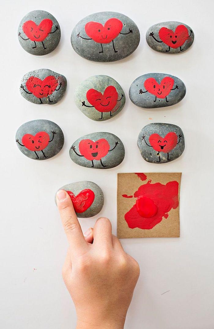 Steine mit Fingerabdrücken dekorieren, Finger in rote Farbe tauchen, Herz gestalten