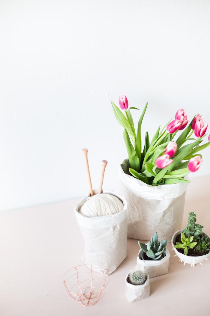 eine weiße wand und ein großer weißer blumentopf aus einer alten weißen papiertüte und mit violetten blumen mit grünen pflanzen, paoiertüten basteln ideen diy