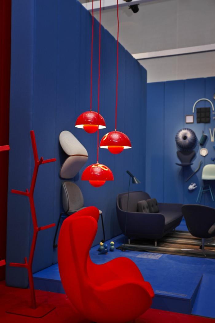 roter Sessel, hängende rote Lampen, Sofa in grauer Farbe, blaue Wände, welche Farbe passt zu Rot