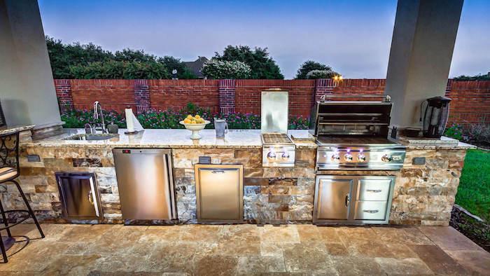 eine kleine outdoor küche mit einem grauen waschbecken, einem ofen und einem elektroherd, ein garten und ein blauer himmel, eine außenküche selber bauen ideen