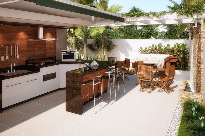 küche mit . einer braunen wand aus holz und mit braunen stühlen aus holz und einem waschbecken und einem elektroherd und ofen, eine außenküche selber bauen, ein garten mkt grünen pflanzen