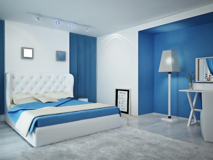 schlafzimmer einrichten ideen, ein bett mit weißen kissen und einer blauen decke, eine weiße lampe und ein grauer teppich, wandfarbe schlafzimmer blau