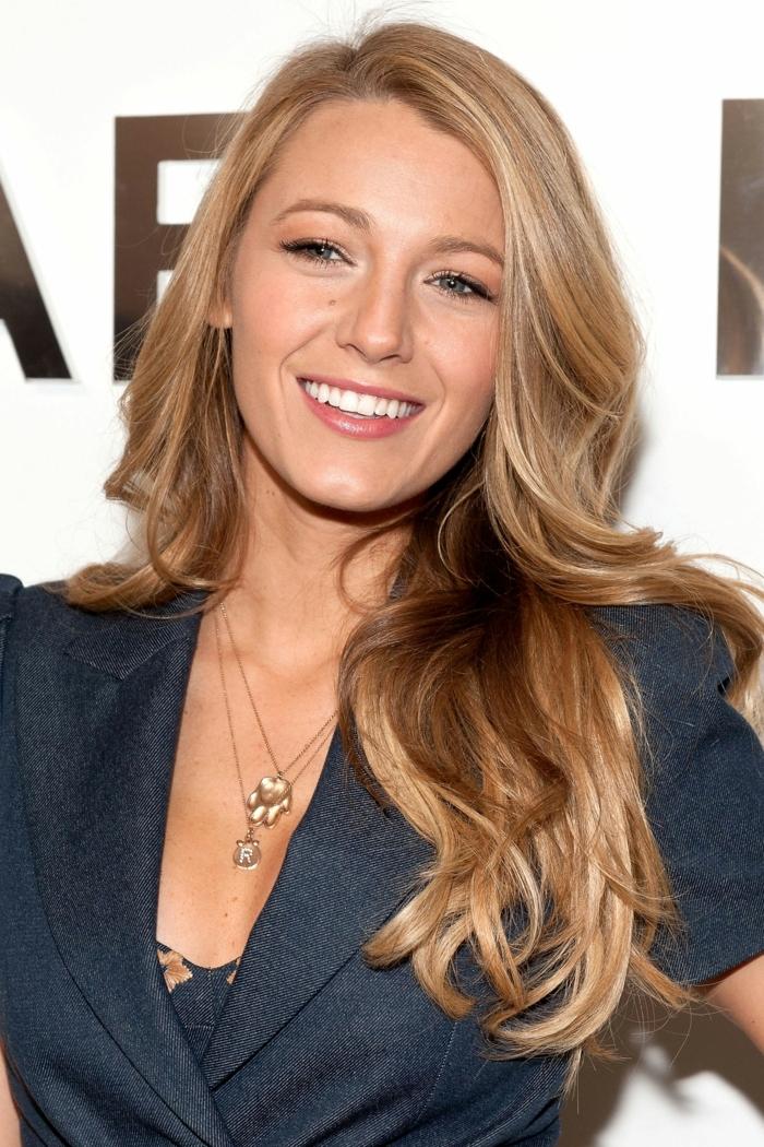 eine schöne Prominente mit bezauberndem Lächeln, blaue Jacke, zwei Ketten mit Anhänger, welche Frisur passt zu mir, lange blonde Haare