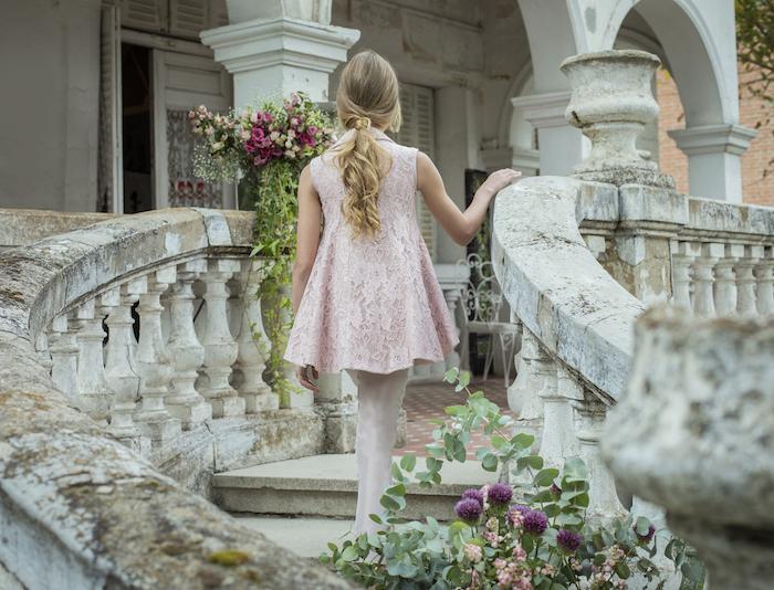 Festliche Frisuren für Kinder, lange blonde Haare, rosafarbenes Spitzenkleid und weiße Strumpfhose