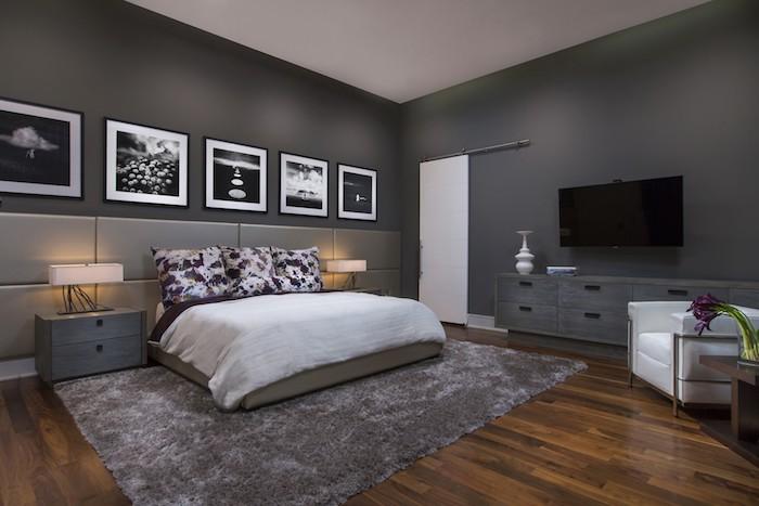 boden aus holz und ein grauer teppich, ein bett mit einer weißen decke und mit kissen mit blumen, schlafzimmer streichen ideen, ein schlafzimmer mit großen grauen wänden