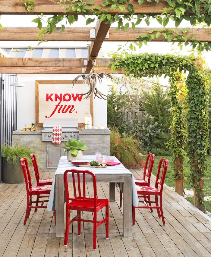 ein boden aus holz, eine miniküche mit einem tisch aus holz und mit roten stühlen, eine weiße vase mit grünen pflanzen, eine outdoor küche selber bauen