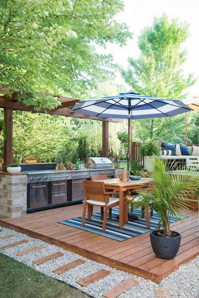 garten mit grünen bäumen und grünen pflanzen, eine miniküche outdoor mit einem blauen sonnenschirm und mit einem braunen tisch aus holz und braunen stühlen, ein kleiner blauer teppich
