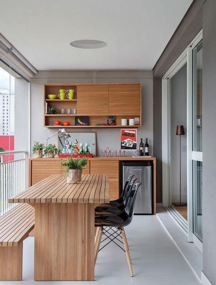 eine wohnung mit grauen wänden und mit einer terrasse mit einem braunen tisch aus holz und mit einem braunen blumentopf mit grünen pflanzen und schwarze stühle und eine kleine graue lampe