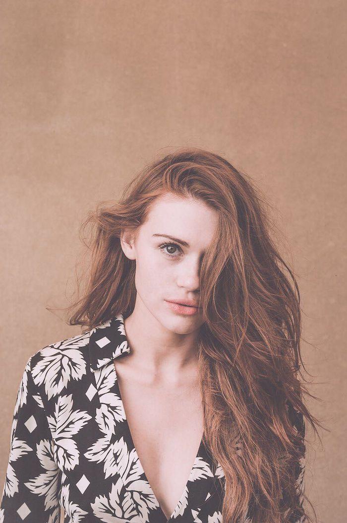 Kupferfarbene lange Haare, heller Hautteint, schwarzes Hemd mit Blumenmuster