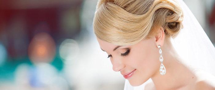 braut make up, frau mit blonden haaren, lange silberne ohrringe, hochsteckfrisur