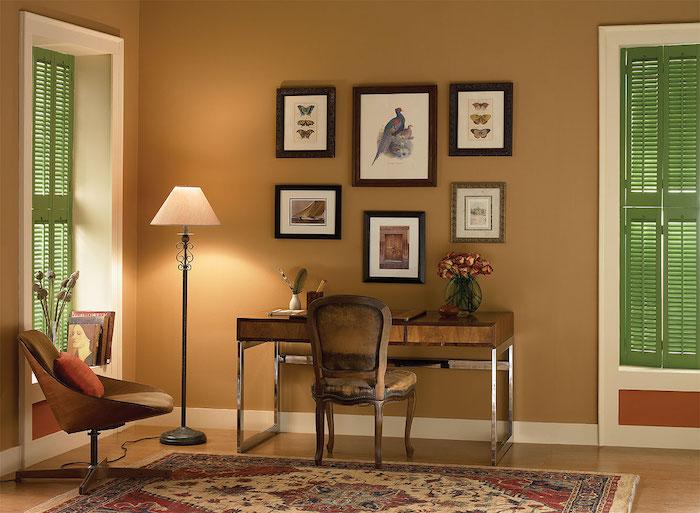 ein büro einrichten, ein stuhl mit einem kleinen orangen kissen und ein teppich, wanddekoration mit vielen bildern und eine weiße lampe, wand farbig streichen