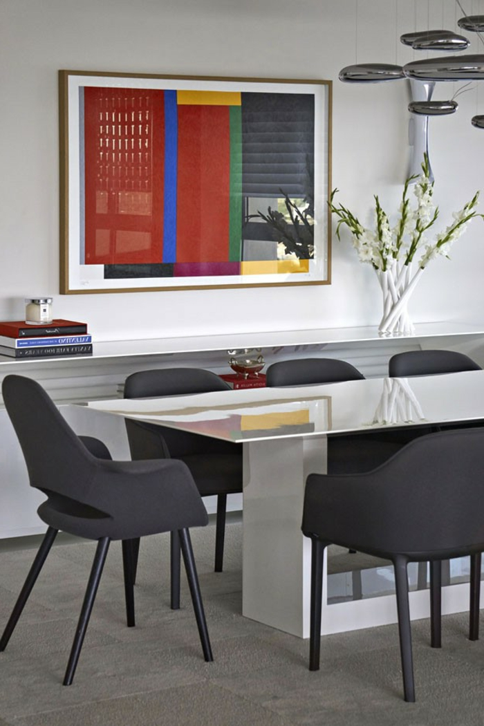 ein Bild mit roten Motiven, weißer Tisch, schwarze Stühle, eine gläserne Vase, welche Farbe passt zu Rot