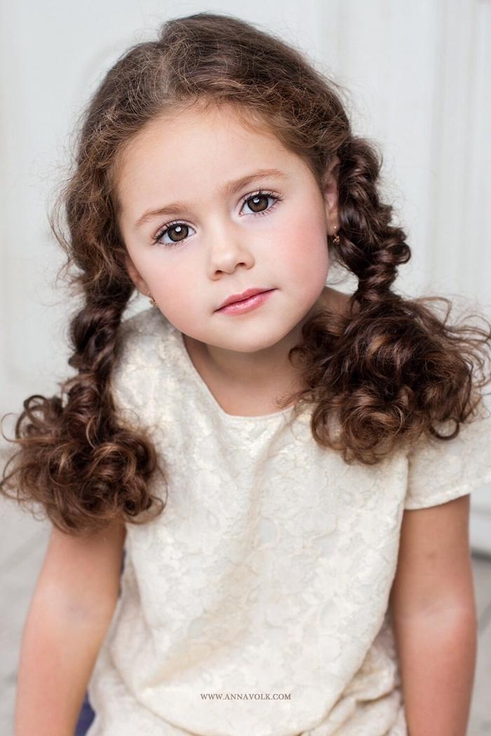 Süßes Mädchen mit langen braunen Haaren und braunen Augen, zwei Zöpfe, weiße Bluse mit kurzen Ärmeln