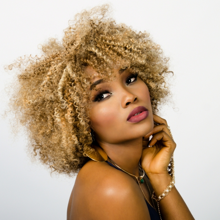 frisuren für feines haar, ideen für natürlich lockige haare, blonde dame, künstlich gefärbtes haar, volle lippen mit rosarotem lippenstift, mandelaugen frau