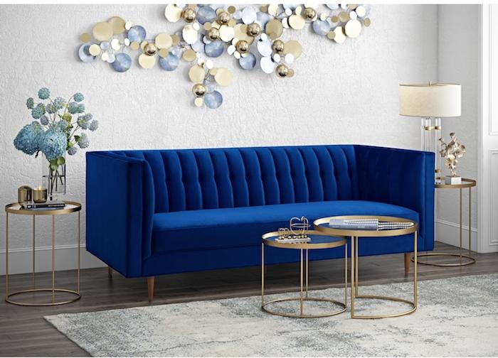 deko ideen wand, blaues designer sofa aus samt, glasvase mit blauen blumen, drei runde tische