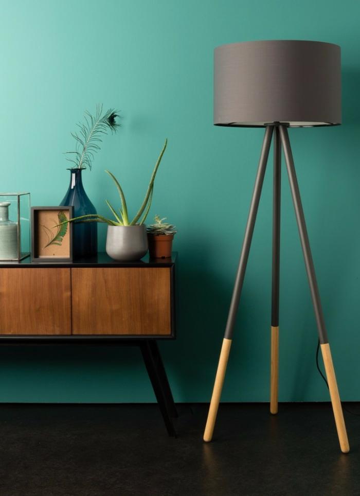 wohnzimmermöbel modern, dunkelgrüne wand schafft naturnahes gefühl, ein kleiner retro schrak mit deko darauf, vase, blume, große stehlampe in grau