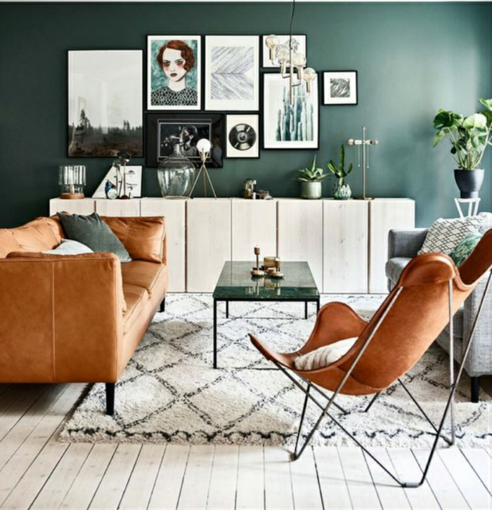 vielfältige deko landhausstil, viele bilder an der wand, stuhl und sofa aus leder, teppich und glastisch, schwarze vase mit weißer blume darin