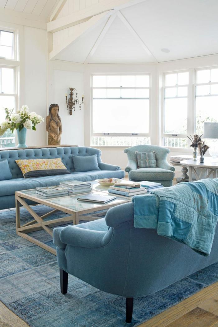 wohnzimmer modern gestalten im landhaus stil weiß und blau, großer raum mit zwei sofas, tisch dazwischen, frische blumen in vase und eine figur von frau