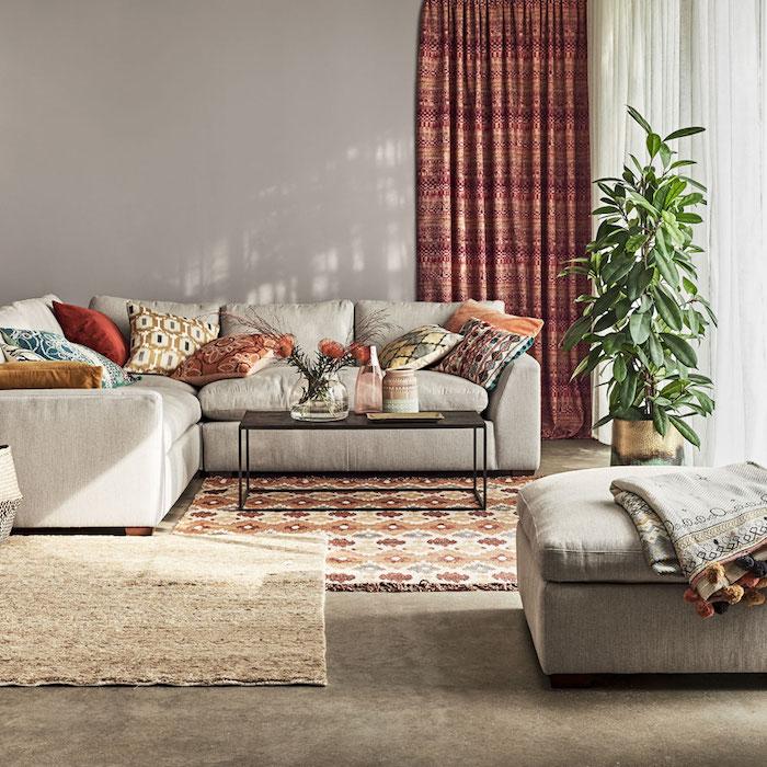 dekoartikel wohnzimmer, hohe grüne zimmerpflange, vorhänge mit ethnischen motiven